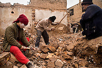 Uighurs break apart bricks in a demolished housing area in the old town of Kashgar, Xinjiang, China.