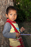 Myanmar, Burma.  Young Burmese Boy in Village near Bagan holding new pencil and two old ones.  He has traces of thanaka paste, a cosmetic sunscreen, on his face.  Burman (Bamar) ethnic group.