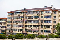 Nanjing, Jiangsu, China.  Apartment Building with Individual Air Conditioners for Each Flat.  Note Solar Water Heaters on Roof.