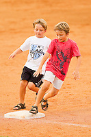 Two young fans run the bases following the South Atlantic League game between the Delmarva Shorebirds and the Kannapolis Intimidators at Fieldcrest Cannon Stadium on August 7, 2011 in Kannapolis, North Carolina.  The Intimidators defeated the Shorebirds 8-3.   (Brian Westerholt / Four Seam Images)
