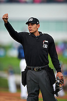 Umpire Richard Genera signals for the bullpen tarps to be covered in between innings during a game between the Cedar Rapids Kernels and West Michigan Whitecaps on June 7, 2015 at Fifth Third Ballpark in Comstock Park, Michigan.  West Michigan defeated Cedar Rapids 6-2.  (Mike Janes/Four Seam Images)