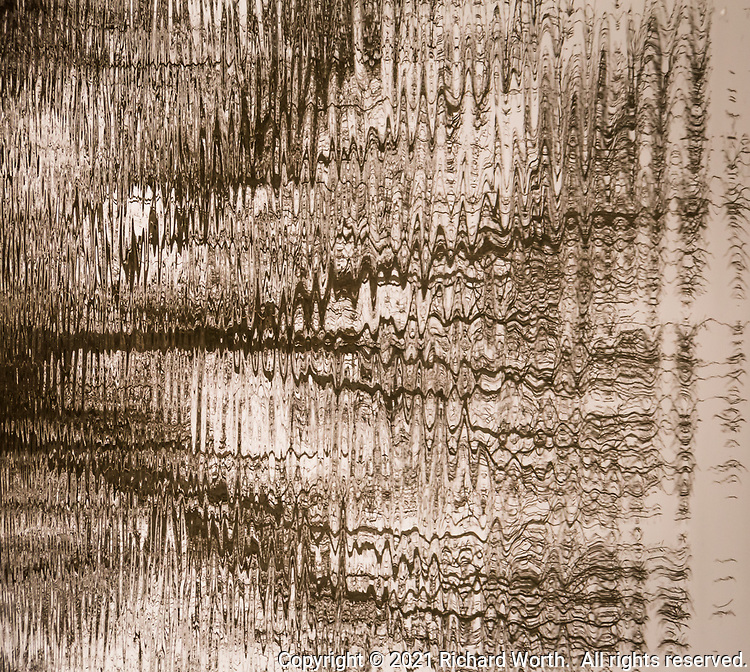 Abstract art created on the surface of a wetland marsh where winter bare tree branches gyrate on rippling water.