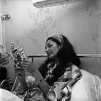 """intérieur d'une chambre d'un hôpital Toulousain. Le 9 juillet 1966. Plan rapproché sur la chanteuse Maria Candido, alitée dans une chambre d'hopital suite à une opération. Elle tient dans ses mains un livre ouvert de Paul Claudel """"Le soulier de satin""""."""