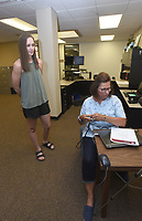 Brielle Myers (left), newly hired math teacher, gets her identification badge and lanyard from Jacki Gustin, human resources administrative assistant at the Rogers school district. Myers will teach seventh grade math at Oakdale Middle School. <br />(NWA Democrat-Gazette/Flip Putthoff)
