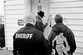 Cleveland, Ohio.March 25, 2008 ..Delivering warning and final eviction notices Detective Robert Kole of the Cuyahoga County Sheriff's Department enters every situation with caution. When the residents are at the home he must assure that all is final and that the home is clear of weapons and that the residents are indeed moving out. ..If no one is there, then he must authorize that the door be forcibly open. He then enters and clears the house at gunpoint in hopes that there are no squatters or inhabitants threaten himself or the movers. He also clears the house for weapons...All emotions and fears are on the surface as some residents greet him by crying on his shoulder while others can threaten him with a weapon..