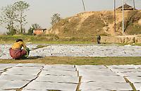Kathmandu Nepal. working with newspaper spread on ground  in Nayapati, Eastern Kathmandu.  33 35