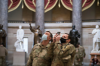 Members of the National Guard take photos in Statuary Hall of the U.S. Capitol, as the House of Representatives vote on H. Res. 24, Impeaching Donald John Trump, President of the United States, for high crimes and misdemeanors, at the U.S. Capitol in Washington, DC, Wednesday, January 13, 2021. Credit: Rod Lamkey / CNP /MediaPunch