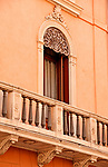 Pink building with an ornate stone balcony; architecture in Padua, Italy
