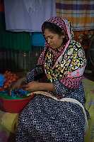 """Rihaa*, 35, lives in a slum in Dhaka with her husband and 3 children. She and her youngest daughter Sumaiya*, 15, work from home doing ornamental stitching, dress decorations and flower chains. """"My daughter works about 2 hours a day to contribute to our family income, but I would never take her out of school"""", says Rihaa*. """"I want all of my children to be independent and get the education that I have never been able to receive."""" Rihaa* doing flower chains in their 1-bedroom house which the whole family shares."""