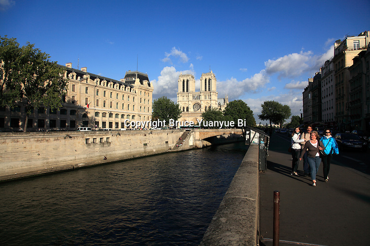 Pedestrians walking on the river bank of Seine with Notre Dame Cathedral in the background. city of Paris. Paris. France