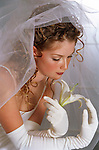 Bride looking at flower, portrait