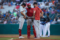 Chattanooga Lookouts pitching coach Rob Wooten (right) has a meeting on the mound with starting pitcher Connor Curlis (23) and catcher Chuckie Robinson (25) during the game against the Tennessee Smokies at Smokies Stadium on July 31, 2021, in Kodak, Tennessee. (Brian Westerholt/Four Seam Images)