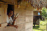 Man in his thatched hut with village's only phone in southern Belize.<br /> <br /> Village:  midway<br /> a Mayan village