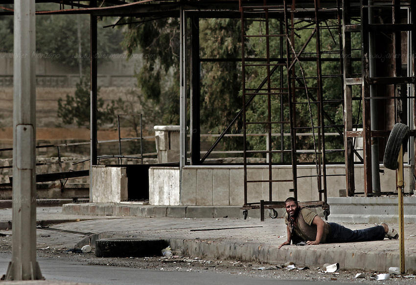 At a moment's notice, the man stood up and began to run towards the members of the Free Syria Army. As he approached the other side of the street, he was shot a second time, falling to the ground. Free Syria Army soldiers crawled through the ground to reach him and pulled them towards a vehicle that rushed him to the hospital. It is not known if he survived. Three civilians were shot on this main road in the space of three hours by the same sniper. ..© Javier Manzano..