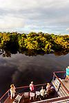 Navigation sur le Rio Negro au nord de Manaus sur le bateau de croisière La JangadaLes nuages et le bateau se reflètent dans les eaux noires du Rio Negro
