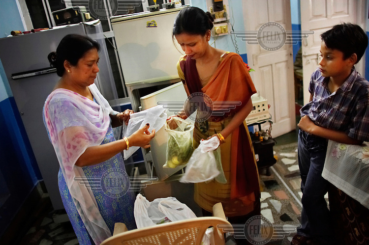 Vindo Gupta, left, helps her daughter-in-law Vanita Gupta unpack groceries from a Reliance Fresh store. Reliance Fresh is the largest in a new wave of western-style supermarkets that have recently opened across India.