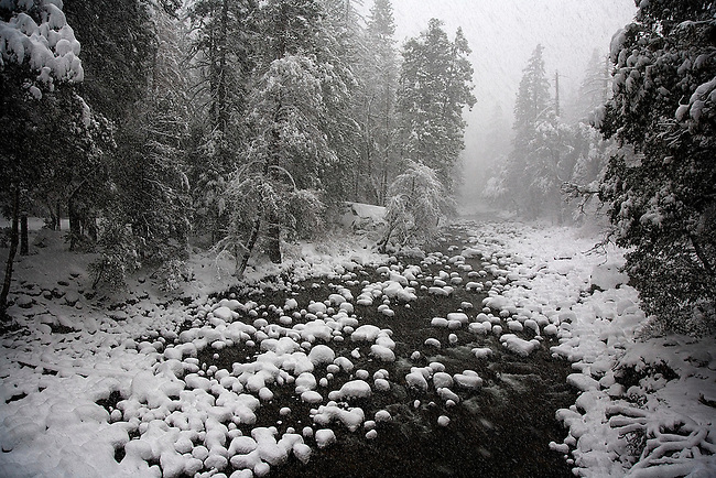 THE MERCED RIVER DURING DRIVING SNOWSTORM IN YOSEMITE NATIONAL PARK, CALIFORNIA