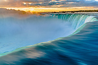 Famous, amazing Niagara Falls horseshoe long exposure close-up in sunrise light with orange mist and clouds, at the border of Canada and USA