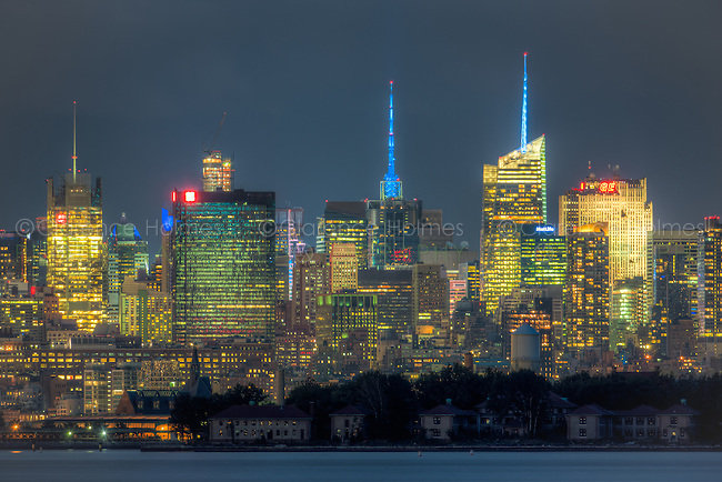 A view of the mid-town Manhattan skyline in New York City during evening twilight including the New York Times Building, One Penn Plaza, the Conde Nast Building, the Bank of America Tower, and the GE Building, with the buildings of Ellis Island in New York Harbor in the foreground.