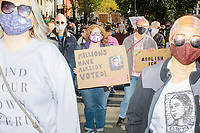 """A crowd gathers in Boston Common for the 2020 Women's March protest in opposition to the re-election of US president Donald Trump in Boston, Massachusetts, on Sat., Oct. 17, 2020.<br /> The sign here features an image of Ruth Bader Ginsburg and reads """"Millions have already voted! / I dissent!"""""""