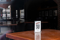 A QR code for a touchless menu stands on an empty table inside the temporarily closed Cask 'n Flagon bar and restaurant across the street from Fenway Park during the ongoing Coronavirus (COVID-19) global pandemic in Boston, Massachusetts, seen here on Wed., Jan. 6, 2021.