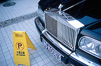 """China. Province of Zhejiang. Hangzhou. A Rools Royce is parked near a roadsign prohibiting any parking. The car's plate wishes """" good luck"""". © 2004 Didier Ruef"""