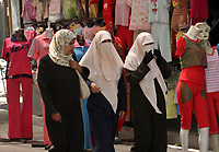 Palestinian women walk next to manikans in the clothes market in Gaza City, Wednesday, Aug. 29, 2007. (FADY ADWAN)
