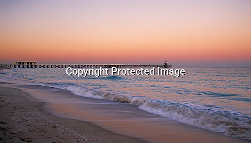 Haulover pier and ocean view at sunset. Gentle waves coming in on the sandy shoreline.
