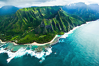 An aerial view of the North Shore of Kaua'i includes Ke'e Beach and beautiful green mountains.
