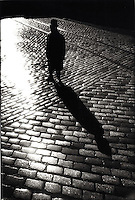 Silhouetted man standing on cobblestone street<br />