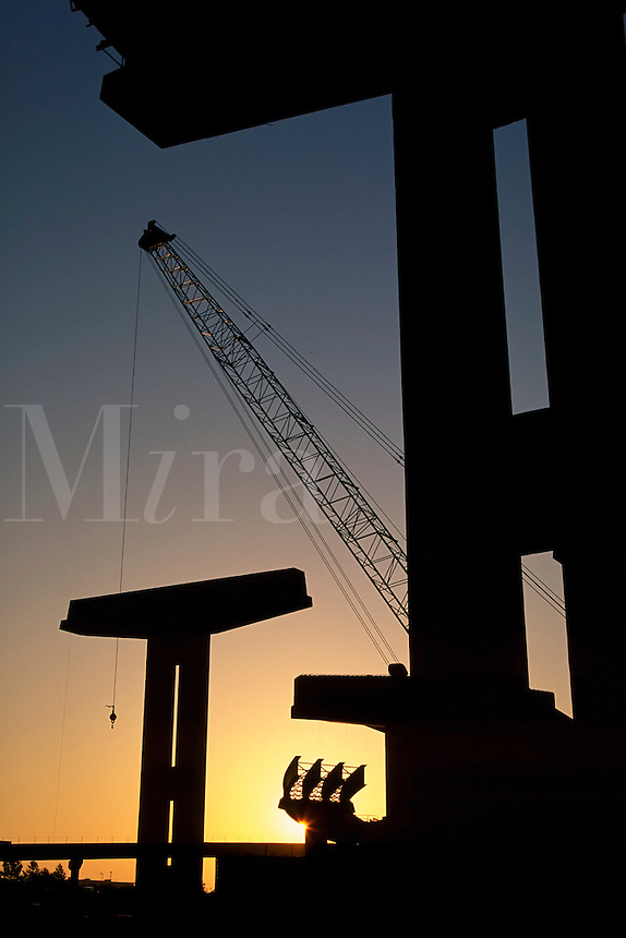 A job site with a tall crane is silhouetted as the sun rises on a highway overpass being constructed.