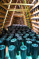 Bottles for sparkling wine standing upside down in a sort of pupitres racks made from palettes. Other bottles in traditional racks. showing the crown caps. Vita@I Vitaai Vitai Gangas Winery, Citluk, near Mostar. Federation Bosne i Hercegovine. Bosnia Herzegovina, Europe.