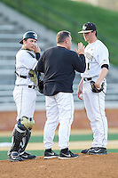 Wake Forest Demon Deacons assistant coach Dennis Healy (31) has a talk with starting pitcher Matt Pirro (1) and catcher Garrett Kelly (28) during the game against the High Point Panthers at Wake Forest Baseball Park on April 2, 2014 in Winston-Salem, North Carolina.  The Demon Deacons defeated the Panthers 10-6.  (Brian Westerholt/Four Seam Images)