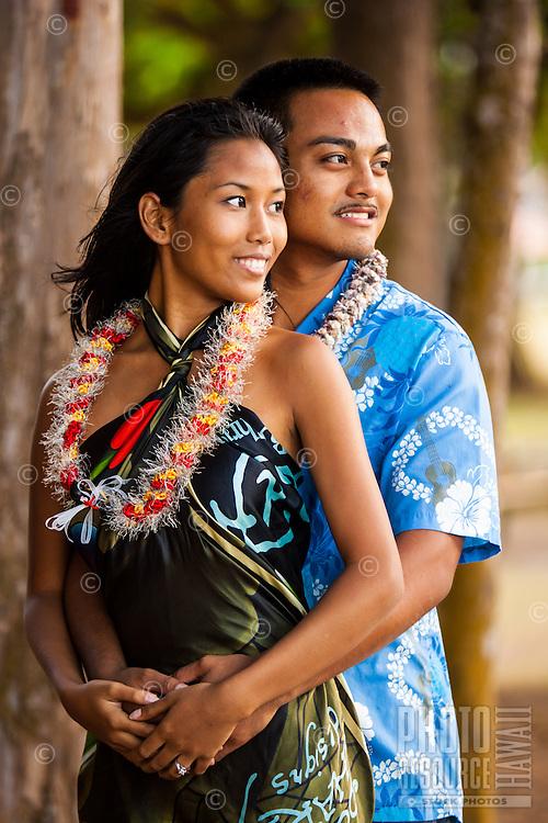 A young, engaged local couple look at the ocean at Kailua Beach Park, Windward O'ahu.