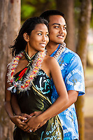 A young, engaged local couple look at the ocean at Kailua Beach Park, Windward O'ahu.