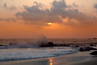Colorful sunset on the famous Palolem beach, with Arabian sea waves crashing on a rock in Goa India