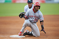 Reniel Ozuna (27) of the Greeneville Reds slides into third base as Nelson Gomez (14) looks on at Calfee Park on June 23, 2018 in Pulaski, Virginia. The Reds defeated the Yankees 6-5.  (Brian Westerholt/Four Seam Images)