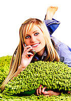 Young woman laying on green shag talking on her cell