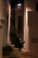 """Italy. Apulia Region. Locorotondo. A lonely young woman seated at night time on a stair takes a selfie with her mobile phone. A selfie is a self-portrait photograph, typically taken with a smartphone which may be held in the hand or supported by a selfie stick. Selfies are often shared on social networking services such as Facebook, Twitter, Snapchat and Instagram. They are for vanity, usually flattering, and are casual in nature (or made to appear casual). """"Selfie"""" typically refers to self-portrait photos taken with the camera held at arm's length. Locorotondo is a town and comune with a population of about 14,000. The city is known for its circular structure which is now a historical center, from which derives its name, which means """"Round place"""". Apulia (Puglia) is a region in Southern Italy. 5.12.18  © 2018 Didier Ruef"""