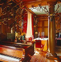 In the living room an antique grand piano covered in framed photographs is situated to one side of a large Doric column