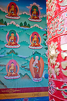 Bodhnath, Nepal.  Buddhist  Prayer Wheel Revolving on Right, Wall Painting in Background, Tsamchen Gompa.