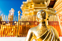 Famous Wat Phra That temple, golden statue with blurred, gold chedi background in Doi Suthep mountains near Chiang Mai Thailand, Southeast Asia