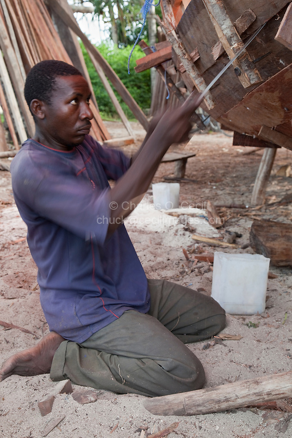 Nungwi, Zanzibar, Tanzania.  Dhow Construction.  Carpenter smoothing the joint between two planks in the hull.