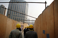CHINA. Shanghai. Construction workers walk through a construction site. Shanghai is a sprawling metropolis or 15 million people situated in south-east China. It is regarded as the country's showcase in development and modernity in modern China. This rapid development and modernization, never seen before on such a scale has however spawned countless environmental and social problems. 2008