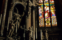 Sculptures of religious figures at the altar with stained glass windows inside the Milan Cathedral, Milan, Italy.