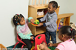 Preschool 3-4 year olds pretend play girl helps herself to food boy is offering
