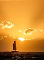 Sailboat at sunset off Kauai coast. Hawaii