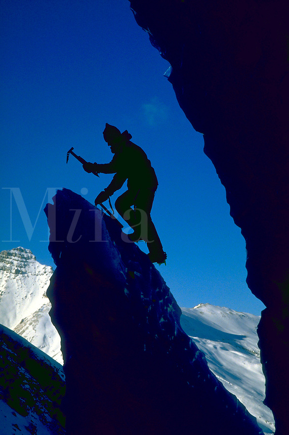 An ice climber on Mount Athabaska silhouetted against blue sky and snow covered mountains in the Canadian Rockies.