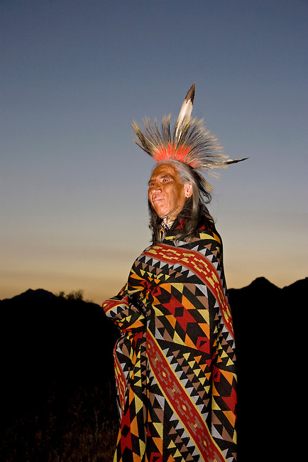 Native American man of the Sioux Nation wrapped in Indian blanket at evening dusk