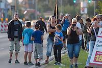 """Nach den pogromartigen Ausschreitungen gegen eine Fluechtlinsunterkunft im saechschen Heidenau am Freitag den 21. August 2015 durch Anwohnerinnen der Ortschaft, kamen am Samstag de 22. August 2015 ca. 250 Menschen in die Ortschaft um ihre Solidaritaet mit den Gefluechteten zu zeigen.<br /> Am Vorabend hatten Rassisten, Nazis und Hooligans sich zum Teil Strassenschlachten mit der Polizei geliefert um zu verhindern, dass Fluechtlinge in einen umgebauten Baumarkt einziehen. Ueber 30 Polizisten wurden dabei verletzt.<br /> Bis in die Abendstunden des 22. August blieb es trotz spuerbarer Anspannung um die Unterkunft ruhig. Im Laufe des Tages wurden immer wieder Gefluechtete mit Reisebussen gebracht was von den wartenenden Heidenauern mit Buh-Rufen begleitet wurde. Vereinzelt wurde auch """"Sieg Heil"""" gerufen, was die Polizei jedoch nicht verfolgte.<br /> Kurz vor 23 Uhr griffen Nazis und Hooligans wie am Vorabend die Polizei mit Steinen, Flaschen, Feuerwerkskoerpern und Baustellenmaterial an. Die Polizei mussten mehrfach den Rueckzug antreten, scheuchte den Mob dann von der Fluechtlingsunterkunft weg. Dabei wurden auch wieder Traenengasgranaten verschossen. Mindestens ein Nazi wurde festgenommen.<br /> Im Bild: Heidenauer warten in den fruehen Abendstunden auf die Ankunft von Fluechlingen.<br /> 22.8.2015, Heidenau/Sachsen<br /> Copyright: Christian-Ditsch.de<br /> [Inhaltsveraendernde Manipulation des Fotos nur nach ausdruecklicher Genehmigung des Fotografen. Vereinbarungen ueber Abtretung von Persoenlichkeitsrechten/Model Release der abgebildeten Person/Personen liegen nicht vor. NO MODEL RELEASE! Nur fuer Redaktionelle Zwecke. Don't publish without copyright Christian-Ditsch.de, Veroeffentlichung nur mit Fotografennennung, sowie gegen Honorar, MwSt. und Beleg. Konto: I N G - D i B a, IBAN DE58500105175400192269, BIC INGDDEFFXXX, Kontakt: post@christian-ditsch.de<br /> Bei der Bearbeitung der Dateiinformationen darf die Urheberkennzeichnung in den EXIF- und  IPTC-Daten ni"""
